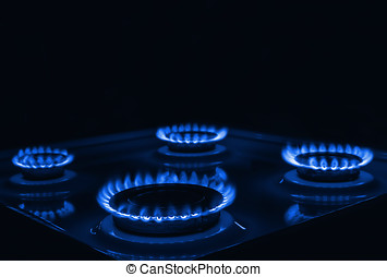 Blue flames of gas burning from a kitchen gas stove with space f