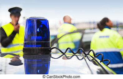Blue flashing light on top of an unmarked police car, with three Emergency Medical Service personnel in the background