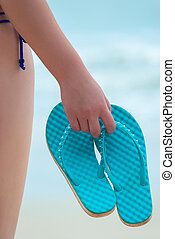 blue flip flops in the hand of a girl on the beach close-up