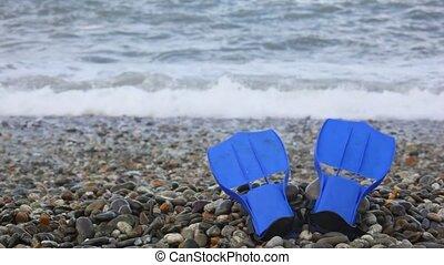 blue flippers on pebble coast against sea surf wave