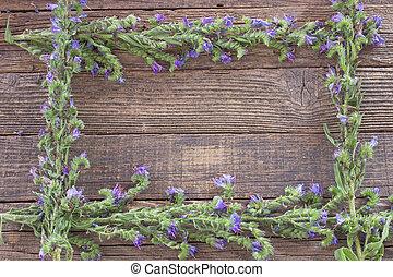 Blue flower frame on wooden background