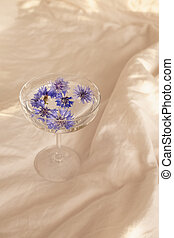 Blue flower heads in a glass with clear water standing on the bed