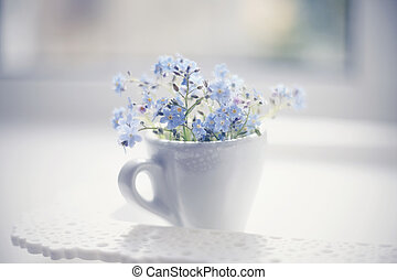 Blue flowers of a forget-me-not in a cup in a window on a lacy tray.