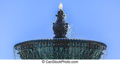 Blue fountain with sparkling water against sky