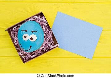 Blue funny donut in box.