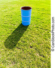 Blue garbage bin casting shadow on green grass.