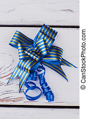 Blue gift bow on white wooden background.