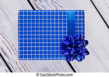 Blue gift box on wooden background.