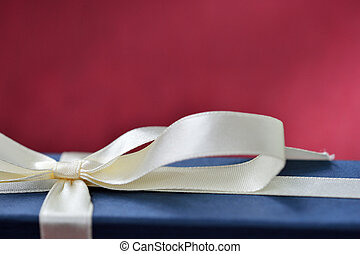 Blue gift box with a bow on a red background