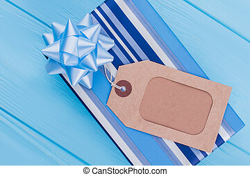 Blue gift box with brown label tag on blue wood.