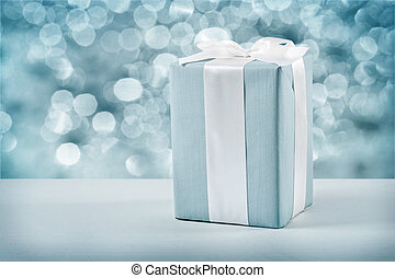 blue gift box with white bow on blurred background