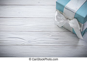 Blue gift box with white ribbon on wooden board celebrations...