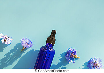 Blue glass bottle with serum and small flowers on blue background
