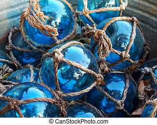 Glass fishing floats with rope knot netting piled in a bucket.