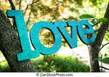 "Blue, glittered, bejeweled word ""Love"" in nature."