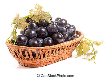 Blue grapes in a wicker basket isolated on white background