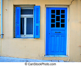 Blue greek shutters window and door in old house