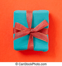 Blue green gift box on red background