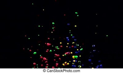 Blue green red and yellow water drops fly up. Black background. Slow motion