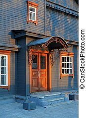 Blue grey wooden house facade in sunset