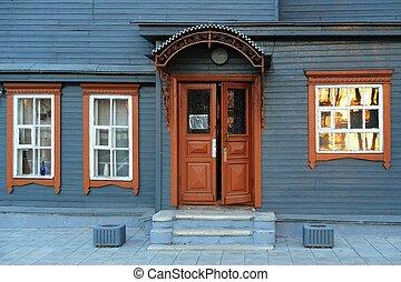 Blue grey wooden house facade with brown open door
