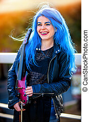 Blue hair woman buskers with violin outdoor in in sun shine.