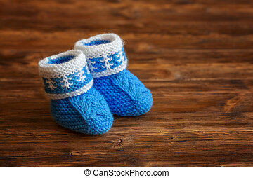 Blue hand made crochet baby booties on wooden background, copyspace