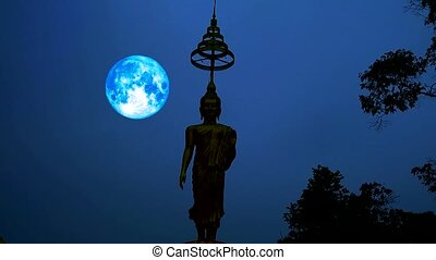 blue harvest moon moving on night sky and silhouette buddha...
