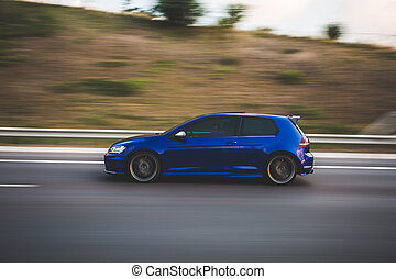 Blue hatchback speed drive on the highway