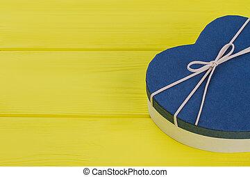 Blue heart-shaped gift box on yellow wood.