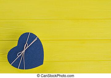 Blue heart shaped gift box on yellow wood.