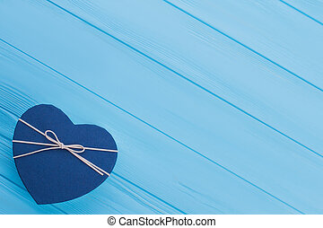 Blue heart shaped gift box with ribbon.