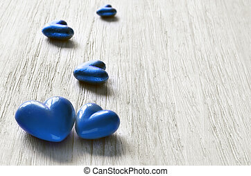 Blue hearts on the wooden background.