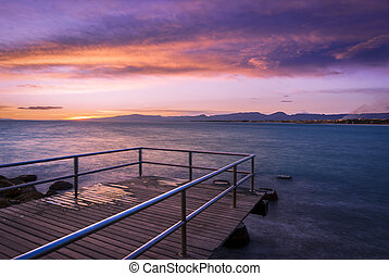 Colorful dark sunset over the sea with a old pier on the foreground.