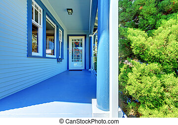 Blue house covered front porch with entrance door.