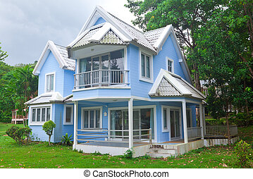 blue house in forest - Beautiful blue house and big tree in...