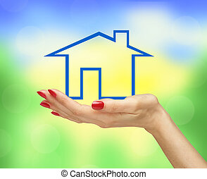 Blue house in woman hand over bright blurred nature background. Real estate