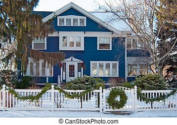 blue house with Christmas wreath on fence