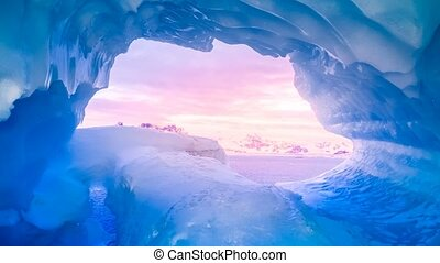 Blue ice cave covered with snow and flooded with soft sunset...