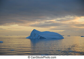 blue iceberg floating in a warm sunset