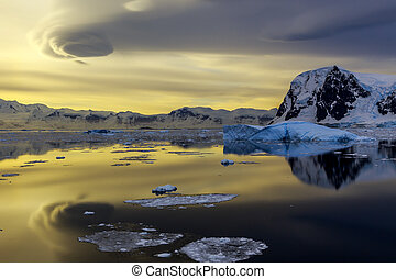 Blue iceberg, mountains and sunset reflecting in ocean at Lemaire Strait, Antarctica