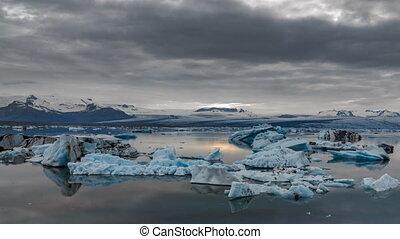 Blue icebergs floating under midnight sun time-lapse -...