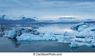 blue icebergs floating under midnight sun - Panning left to...