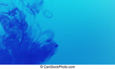 blue ink cloud poured in blue water in slow motion