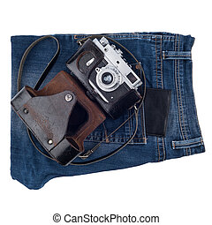 Blue jeans and an old camera isolated on white background.