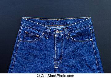 Blue jeans on dark background.