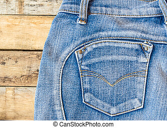 Blue jeans on old wooden surface