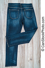 Blue jeans on  wooden background .