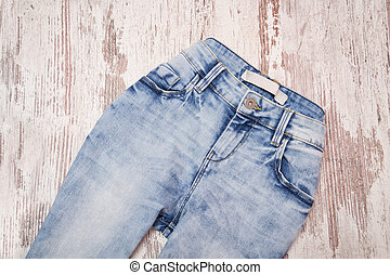 Blue jeans on wooden background. Fashionable concept