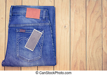 Blue jeans on wooden background top view
